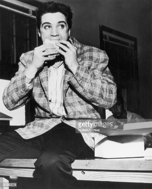 American singer and actor Elvis Presley sitting on a bench eating a sandwich Memphis Tennessee