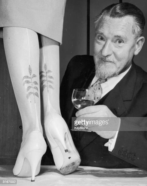 Man examines a prototype of a new range of hand-painted stockings with a leaf motif by the designer Elsa Schiaparelli.