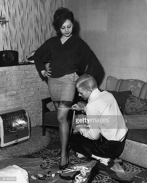 Surrounded by cotton reels and a sewing kit pop singer Johnny Dee kneels to take his wife Lola's thigh measurement for a pair of slacks which he is...