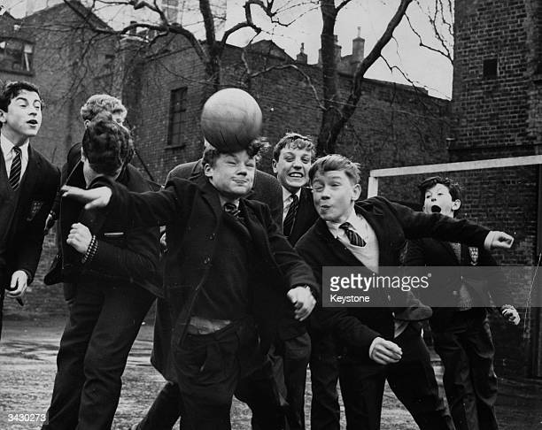 Dennis Rofe and Terry Brisley both aged thirteen head a football in the playground of their school Davenant Foundation Grammar School Stepney London...