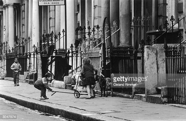 A group of children and their dog playing on Cricklewood Broadway in London's Notting Hill