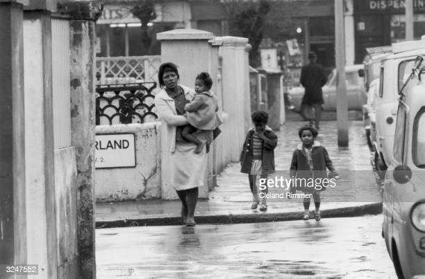 West Indian woman and her three children walk down a street in London's Notting Hill.