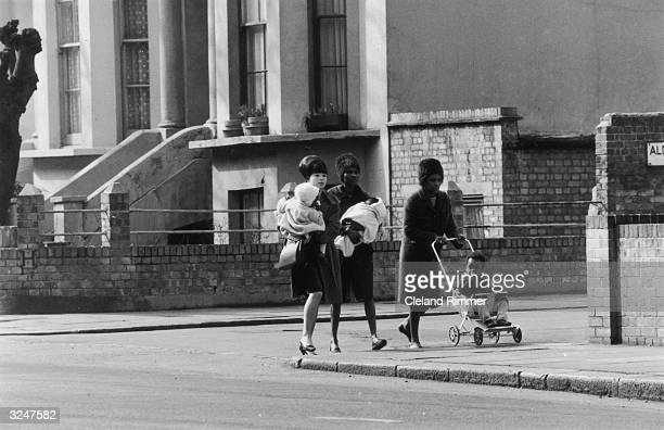 West Indian women walking with their children down a street in London's Notting Hill.
