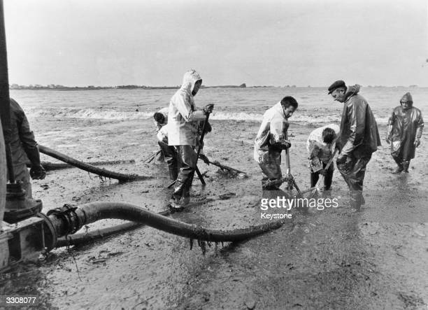 Firemen at work on a beach in Brittany pumping away crude oil which spilled from the wrecked oil tanker 'Amoco Cadiz' off the French coast