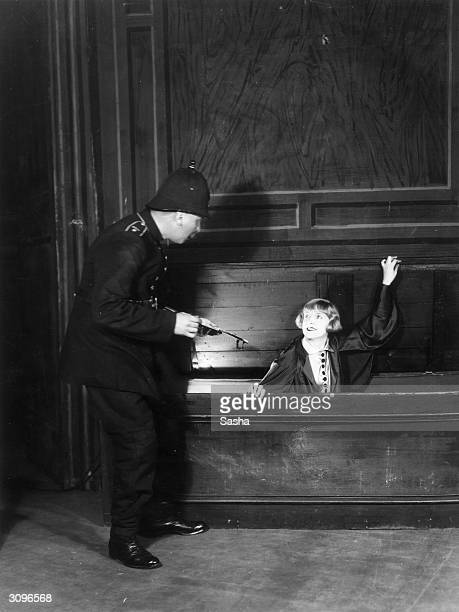 Actress Florrie Groves emerges from a coffin like a vampire to the astonishment of a policeman in a scene from 'The Strangler' at the Kilburn Empire
