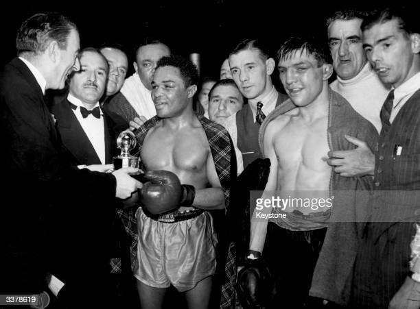 American boxer Henry Armstrong being presented with a championship trophy after a Welter Weight fight at Harringay arena against Ernie Roderick