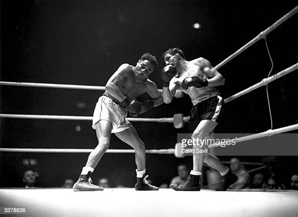 British boxer Ernie Roderick landing a punch during a Welter Weight title fight at Harringay Arena against the holder American Henry Armstrong