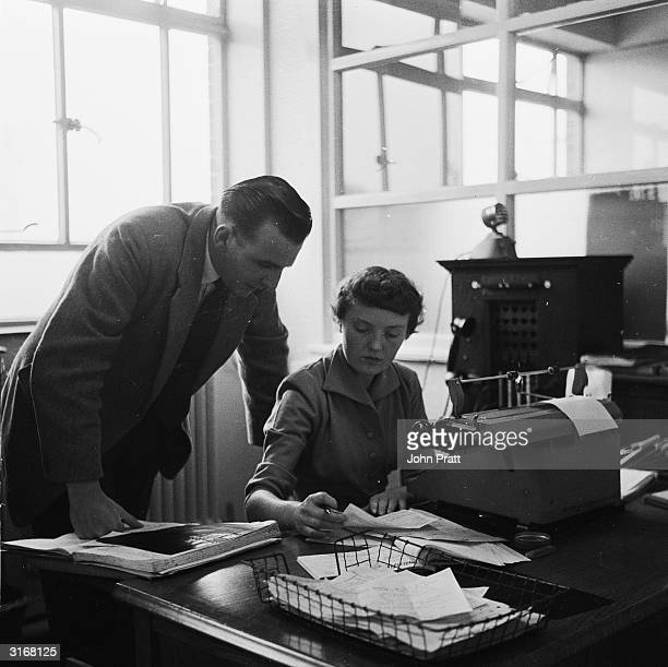 A secretary checks the work to be done with her manager