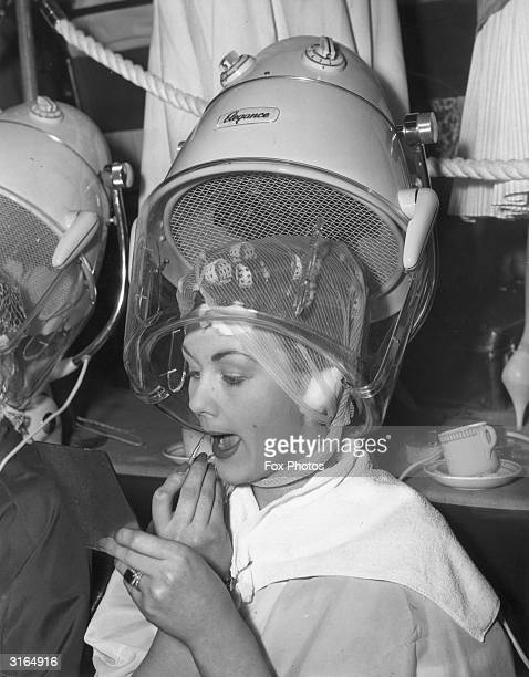 Model Susan Livesey retouching her lipstick underneath the hairdryer at the International Hairdressing Exhibition of Great Britain at the...