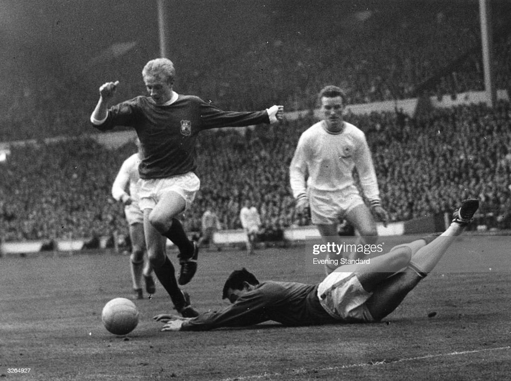 Leicester City goalkeeper Gordon Banks dives at the feet of Manchester United's Denis Law during the FA Cup Final at Wembley. United won 3-1.