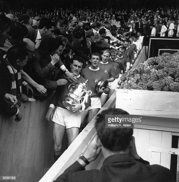 Manchester United captain Noel Cantwell leads his team past admiring fans from the Royal Box after receiving the FA Cup trophy on beating Leicester...
