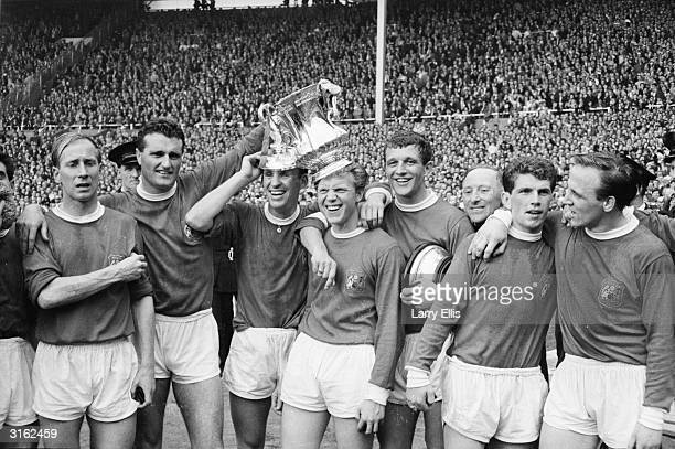 Members of the Manchester United football team celebrating after beating Leicester City in the FA Cup final including Bobby Charlton Noel Cantwell...