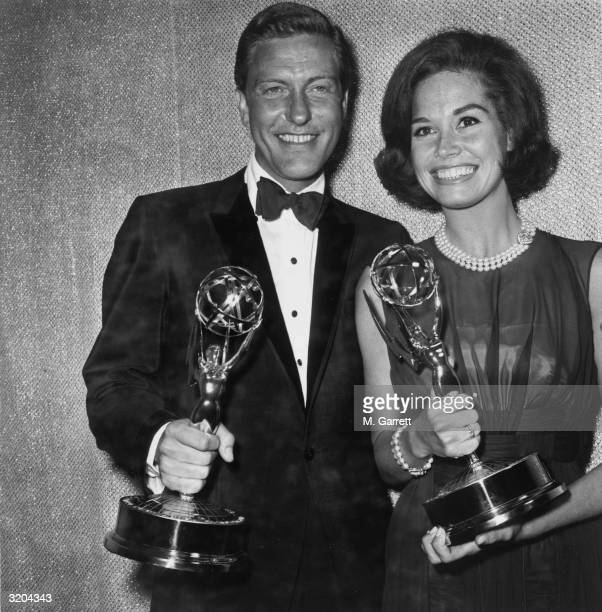 American actors Dick Van Dyke and Mary Tyler Moore smile while holding the Emmy Awards they won for Best Actor and Actress for the television series...