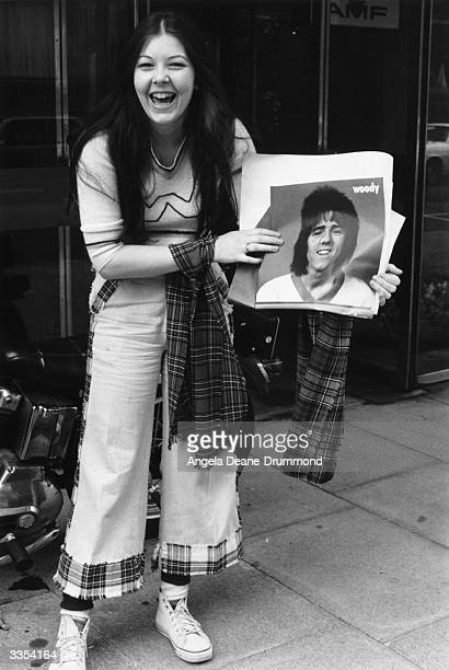 A young fan of the Scottish pop group Bay City Rollers wearing tartan clothing holding a poster of guitarist Stuart 'Woody' Wood