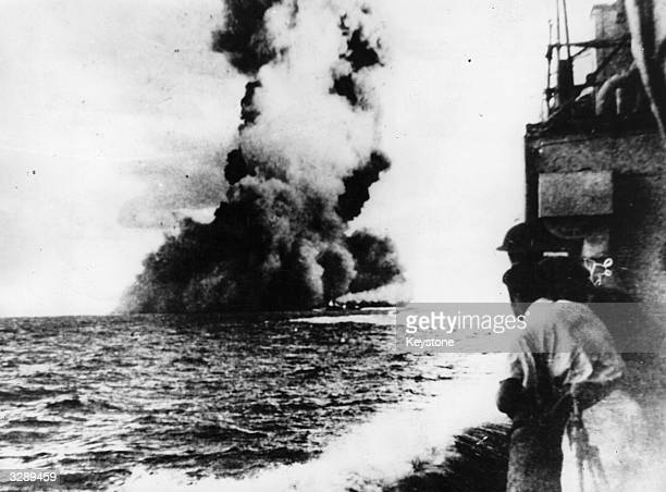 A black pall of smoke hangs over the water off the Libyan coast marking the grave of the British 31000ton battleship 'Barham' which blew up when hit...
