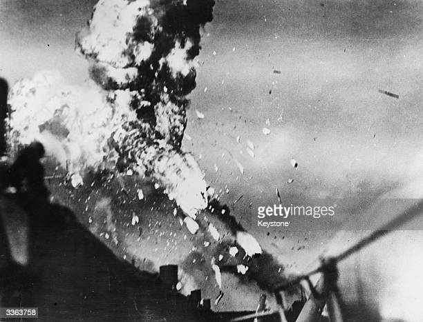 Gasoline flames and molten metal bursting from the body of a Japanese Kamikaze plane which dived into the deck of the USS Intrepid during World War...