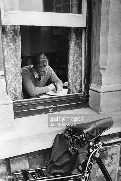 An undergraduate at Oxford University working in his lodgings his trusty bicycle tethered outside the window Original Publication Picture Post 5159...