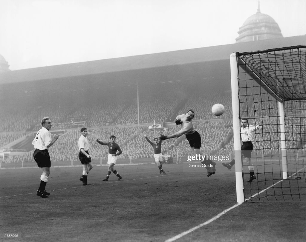 England captain Billy Wright (left), and team mate Alf Ramsey, in the net, look on anxiously as goalkeeper Gil Merrick tips a shot round the post during a Hungarian attack at the England goal during the international match at Wembley. England lost 6-3.