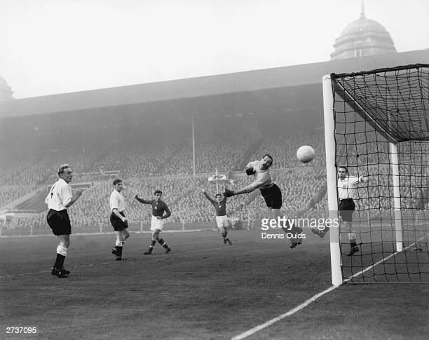 England captain Billy Wright and team mate Alf Ramsey in the net look on anxiously as goalkeeper Gil Merrick tips a shot round the post during a...