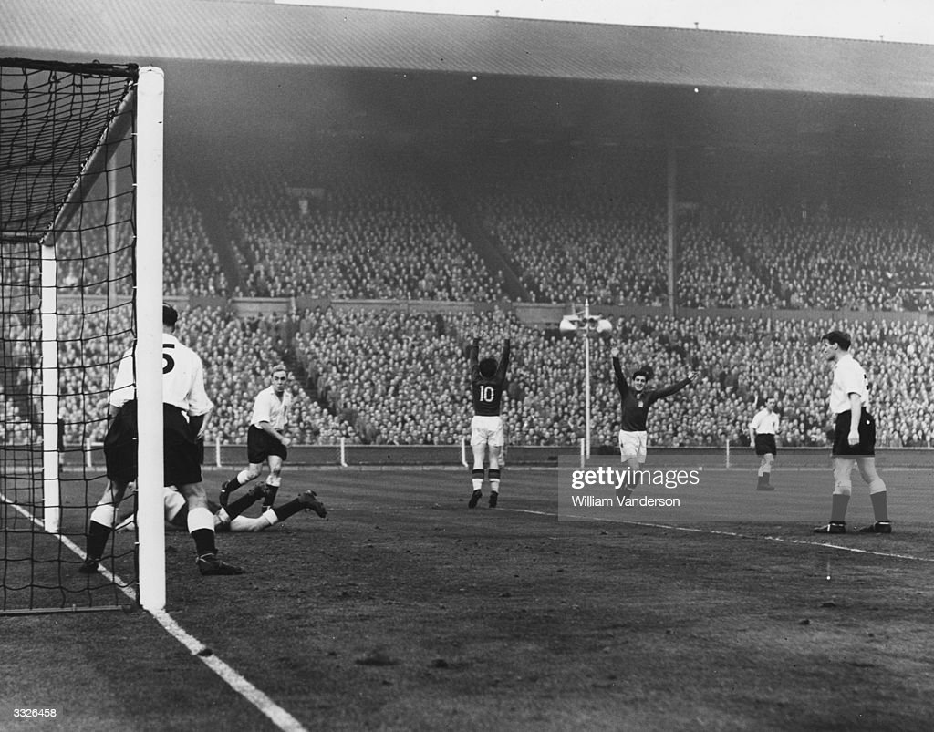 Hungary's third goal is scored by the team captain Ferenc Puskas (number 10) during their match against England at Wembley Stadium.