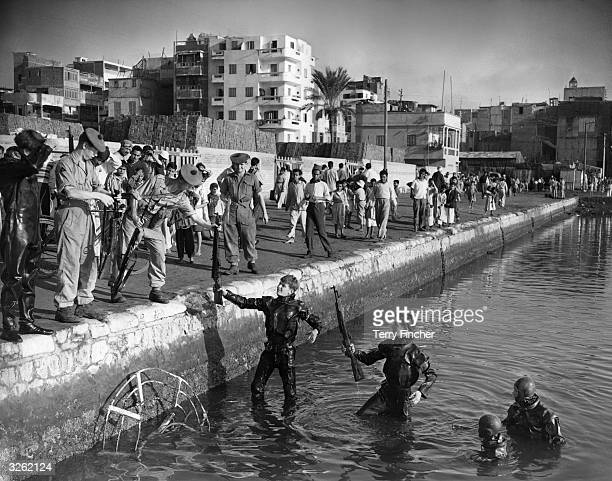 British frogmen recovering arms found in the Bassain Industrielle Port Said The arms are being handed over to members of the Argyll and Sutherland...