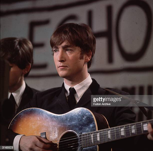 John Lennon singer guitarist and songwriter with the Beatles plays an acoustic guitar during Granada TV's Late Scene Extra television show filmed in...