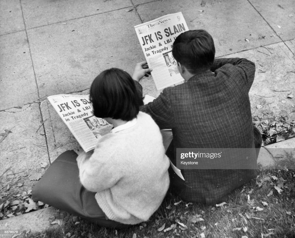 Two people in Lafayette Park, Washington, reading the newspaper reports of President John F Kennedy's assassination.