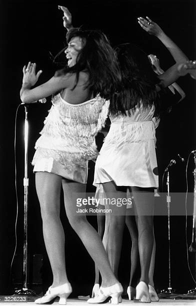 Fulllength image of American rock singer Tina Turner and her female backup dancers waving their arms in the air as they dance on stage during a...