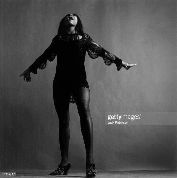 Fulllength studio portrait of American rock singer Tina Turner wearing a dark crocheted minidress singing while looking up and stretching her arms...