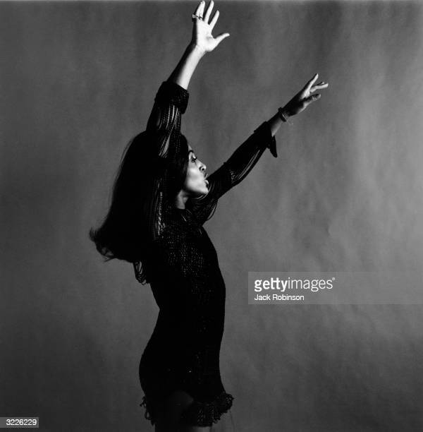 Studio portrait of rock singer Tina Turner wearing a dark crocheted minidress dancing in profile with her arms over her head while singing New York...