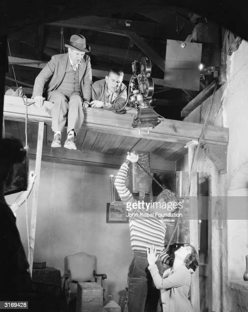 Director Tod Browning in hat perches on the roof of the set watching John Gilbert threatening to beat a pleading Renee Adoree in a dramatic scene...