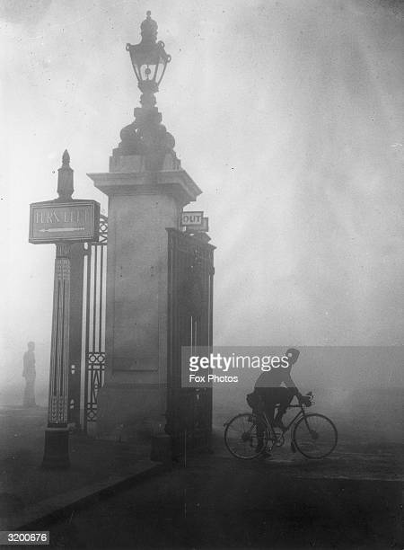 A cyclist stops to find his way through the thick fog at Hyde Park Corner London Fog like this is known by the nickname 'pea souper'