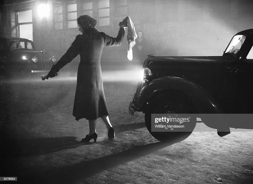 A woman leads a car through London's Regent's Park with a torch, during the thick fog with visibility reduced to a few yards.