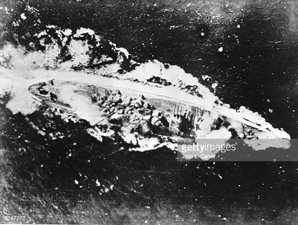 The massive Japanese battleship Yamato receives two direct hits from US dive bombers in the Tablas Straits of the Philippines. Lieutenant Commander...