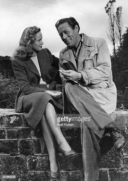 Rex Harrison the British leading actor shares a joke with Peggy Cummins during the filming of 'Escape' for TCF directed by Joseph L Mankiewicz...