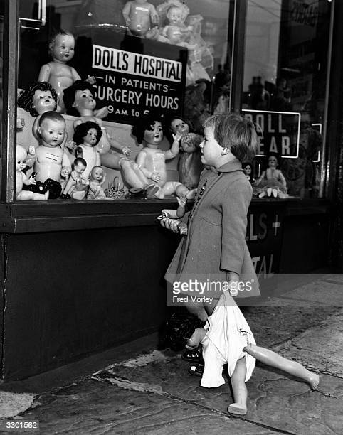 Fouryearold Susan Crick of Hammersmith London looking into the window of her local Doll's Hospital run by Barry and Jean Elder She has brought her...