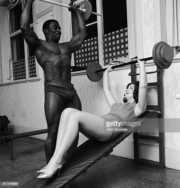 25th October 1963, Linda Nicoll practises weightlifting under the expert supervision of Herbert Dennis, Mr Jamaica of 1963.