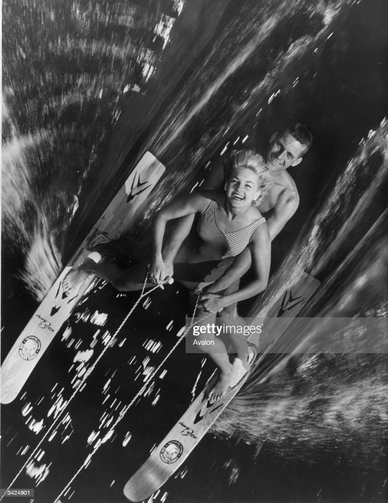 Two water-ski champions on one pair of skis captured by a photographer in an overhanging tree as they speed past at Cypress Gardens, Florida.