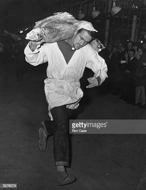 Ted Clift winning the carcass carrying race held to celebrate the centenary of the London Central Markets at Smithfield market Other events included...