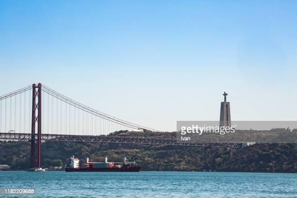 25th of april bridge lisbon portugal and christ the king statue with view of lisbon portugal - statua di cristo re foto e immagini stock