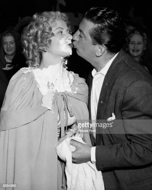 Actress Margaret Lockwood who has just had a pie thrown in her face in the film 'Cardboard Cavalier' receives a consolation kiss from costar Sid...