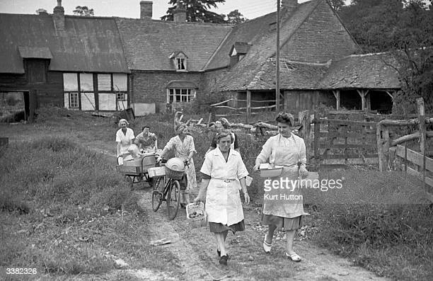 Members of a Women's Institute canning club at AshtonunderEdge Vale of Evesham on their way to the village hall with their sugar ration and fruit for...