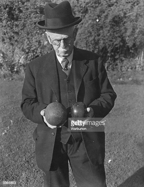 Mr H W Walton 84yearold president of the Lewes Castle Bowling Green Society comparing a bowl used on a modern flat green and one used on a...
