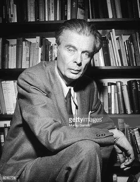 EXCLUSIVE Portrait of British author Aldous Huxley leaning his forearm on top of his knee in front of bookshelves at his home in Los Angeles...