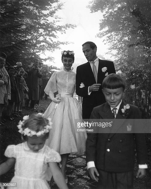 Film star couple Audrey Hepburn and Mel Ferrer walk arm in arm on their wedding day. Dress designed by Balmain.