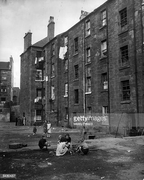 Children play on waste ground outside a tenement block in Camden Street, the Gorbals, Glasgow. The tenements were built quickly and cheaply in the...