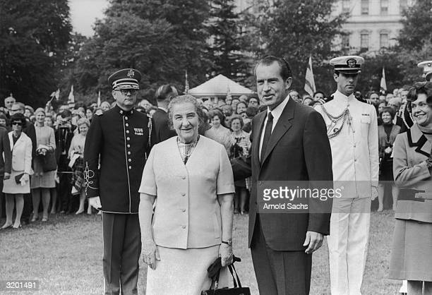 Israeli Prime Minister Golda Meir poses with American President Richard M. Nixon while a crowd watches in the background on the lawn of the White...