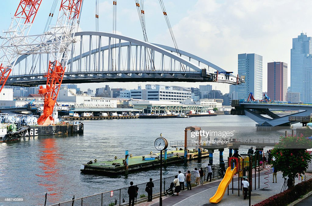 A 2,600-ton new bridge is adjusted to connect to the roads, lifted by a huge crane on May 8, 2014 in Tokyo, Japan. The 120-meter bridge, assembled at Yokohama Port not to disturb the traffic of the Sumida River, will be part of Loop Line 2 which is an expected major traffic artery linking major venues at the 2020 Tokyo Summer Olympics.