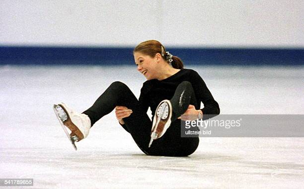 Sportlerin Eiskunstlauf D sitzt nach einem Sturz auf dem Eis