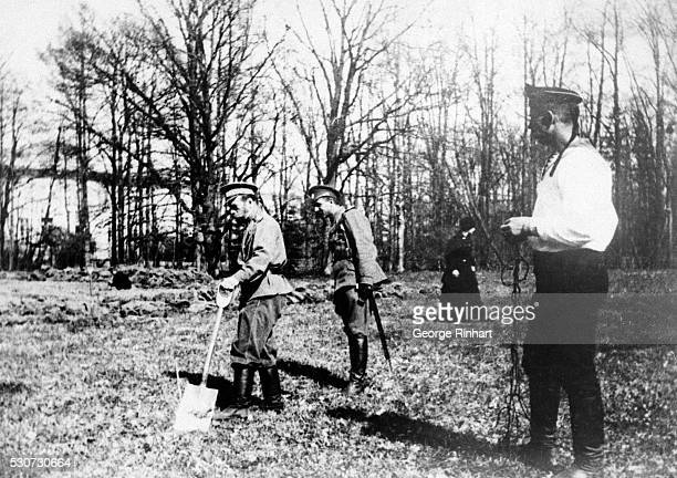 2/6/1921TsarkoeSelo Russia The internallyexiled Czar Nicholas II of Russia working in the kitchen garden Behind him is the officer of the guard To...